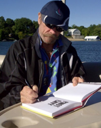Edward Finstein (Wine Doctor) on Musselman's lake signing his new book. Photo – Rick Wigmore