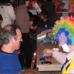 Doo Doo the Clown paints Ian Feld's face while Ian paints Doo Doo's hair.